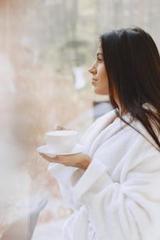 Dzień dobry. kobieta pije kawę. pani przy oknie.