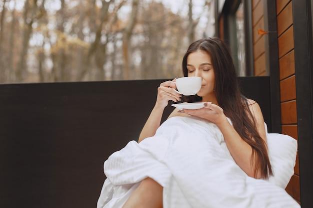 Dzień dobry. kobieta w kocu. pani siedząca na tarasie. brunetka pije kawę.