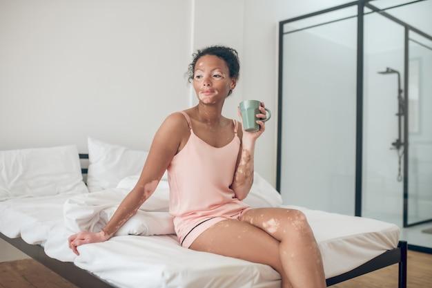 Dzień dobry. młoda kobieta delektująca się poranną herbatą ziołową i wyglądająca na zadowoloną