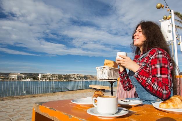 Dzień dobry. młoda kobieta o francuskim śniadaniu z kawą i rogalikiem, siedząc na zewnątrz na tarasie kawiarni nad morzem.