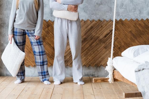Dzień dobry. młoda para stoi przy ścianie z poduszkami. nowy dzień przed nami.