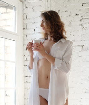Dzień dobry! piękna kobieta ubrana w białą bieliznę pijąca kawę rano siedząc przy oknie.