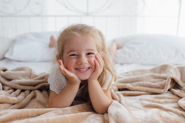 Dzień dobry. przyjemne przebudzenie dla małej dziewczynki, dziewczyna o poranku wygląda wesoło i pełna energii. porady o przyjemny poranek każdego dnia. ciesz się przebudzeniem i czuj się dobrze.