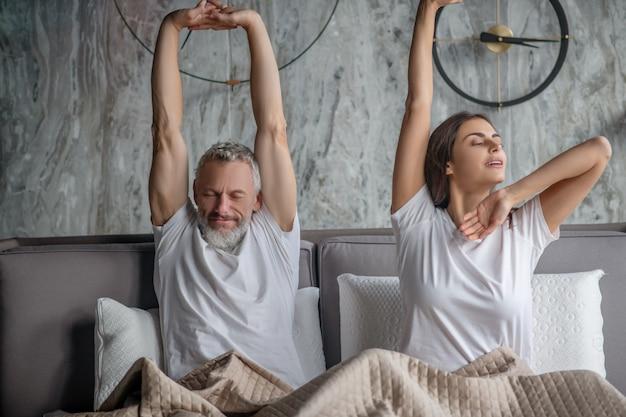 Dzień dobry. siwy mężczyzna i ciemnowłosa ładna kobieta budzą się w dobrym nastroju, rozciągając się w łóżku