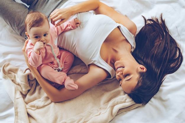 Dzień dobry słoneczko! widok z góry wesołej pięknej młodej kobiety przytulającej swoją córeczkę podczas leżenia w łóżku