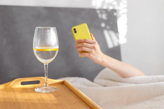 Dzień dobry, szklanka wody z cytryną, śniadanie w łóżku, detoks, właściwy poranek, pozytywne wibracje, zdrowe odżywianie, miłość własna, kobieta w łóżku, słoneczny dzień, weekend, woda, szkło