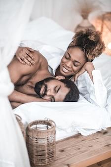 Dzień dobry ... uśmiechnięta młoda ciemnoskóra kobieta w białej koszuli patrząc na śpiącego męża dotykającego jego ramienia