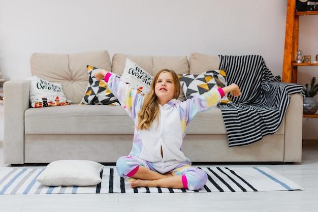 Dzień dobry w domu. dziewczynka budzi się ze snu mała dziewczynka siedzi na podłodze w piżamie kigurumi i wyciąga się ze snu