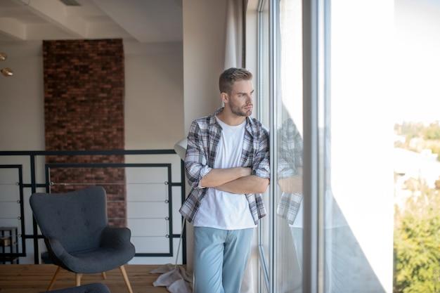 Dzień dobry. zamyślony mężczyzna stojący przy panoramicznym oknie