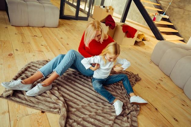 Dzień Domowy. Niesamowity Blond Dzieciak Siedzi Na Podłodze I Bawi Się Z Mamą Premium Zdjęcia