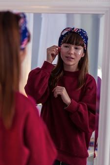 Dzień domowy. wesoła uczennica, która podczas przygotowań do imprezy używa opasek na oczy