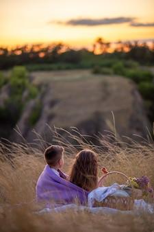 Dzień dziecka. dzieci o zachodzie słońca siedzą na pikniku.