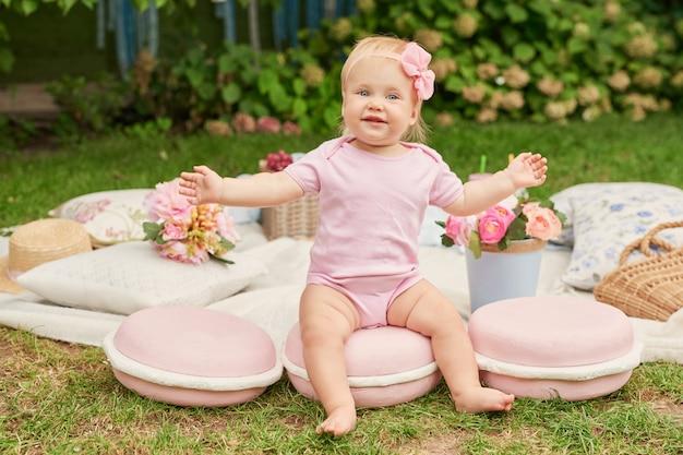 Dzień dziecka, dziewczynka w parku siedzi w koszu z makaronikami na letnim pikniku