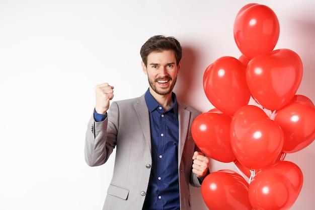 Dzień kochanków. wesoły młody człowiek w garniturze, czując się pewnie o randce walentynki, mówiąc tak i uśmiechając się, stojąc w pobliżu balonu serca, białe tło.