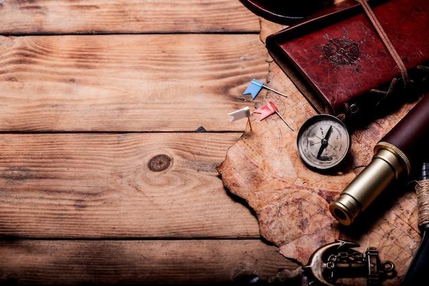 Dzień kolumba. piraci i skarby z mapą świata i sprzętem do odkrycia. skopiuj miejsce na ciemnym tle.