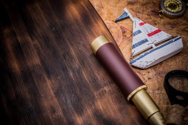 Dzień kolumba. vintage mapa świata i sprzęt do odkrycia. skopiuj miejsce na ciemnym tle drewna.