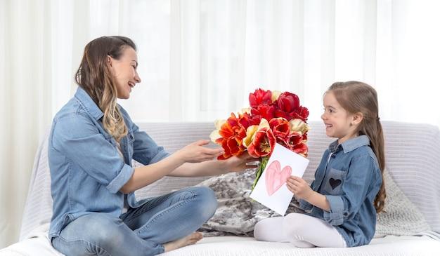 Dzień matki. córeczka z kwiatami gratuluje mamie