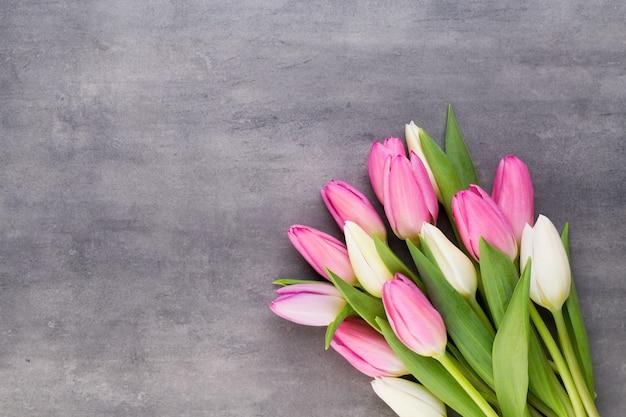 Dzień matki, dzień kobiety, wielkanoc, różowe tulipany, prezenty na szarym tle.
