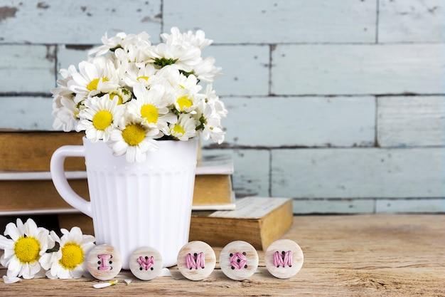 Dzień matki koncepcje kwiatów stokrotka w biały kubek z haftem mama i kocham