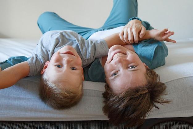 Dzień matki. matczyna miłość. szczęśliwa kobieta i chłopiec w niebieskim uścisku tkaniny. . skopiuj miejsce. gra z synem