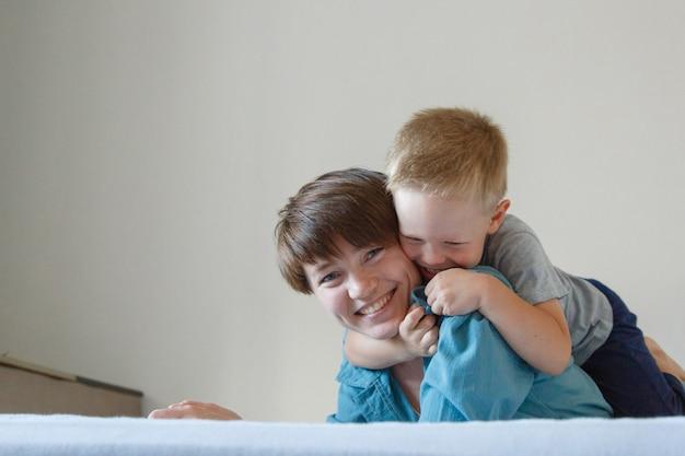 Dzień matki. matczyna miłość. szczęśliwa kobieta i chłopiec w niebieskim uścisku tkaniny