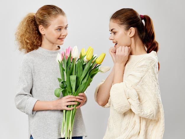 Dzień matki, młoda kobieta z dzieckiem pozująca do kwiatów, prezent na dzień kobiet i dzień matki