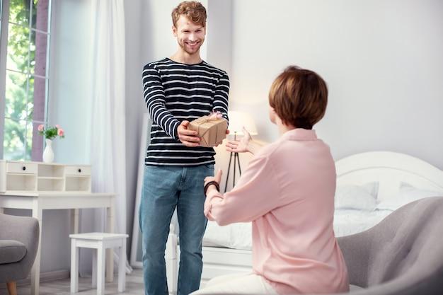 Dzień matki. radosny młody człowiek trzymający prezent gratulując matce