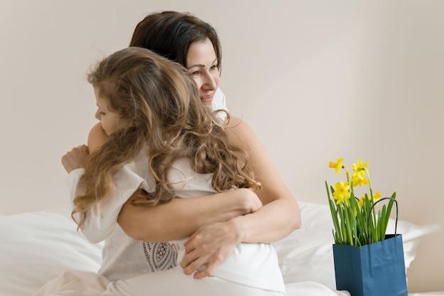 Dzień matki. rano, mama i dziecko w łóżku, matka przytula swoją córeczkę.