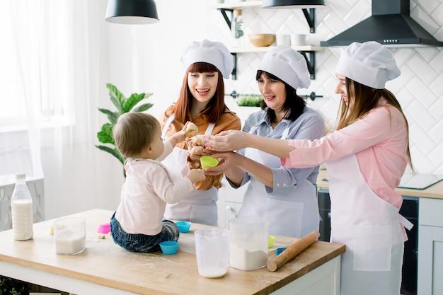 Dzień matki, rodzina, gotowanie i koncepcja ludzi - mała śliczna dziewczynka i jej mama, ciocia i babcia robią i dekorują babeczki w domowej kuchni