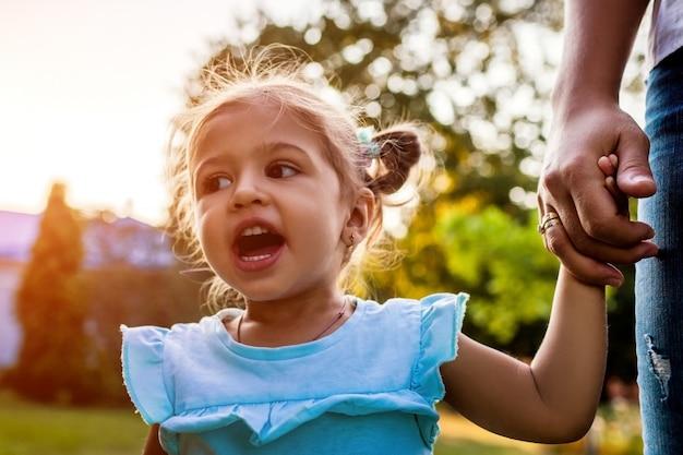 Dzień motehra. mała berbeć dziewczyna krzyczy outdoors. macierzysta mienie córki ręka w parku.