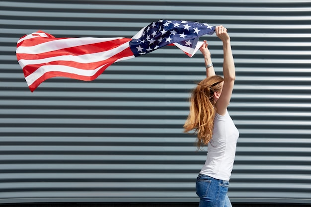 Dzień niepodległości i koncepcja patriotyczna. aktywna dziewczyna z długimi rudymi włosami biegnącymi z machaną przez wiatr flagą usa