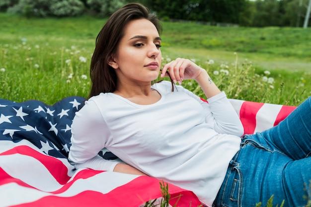 Dzień niepodległości pojęcie z kobietą i flaga amerykańską na trawie