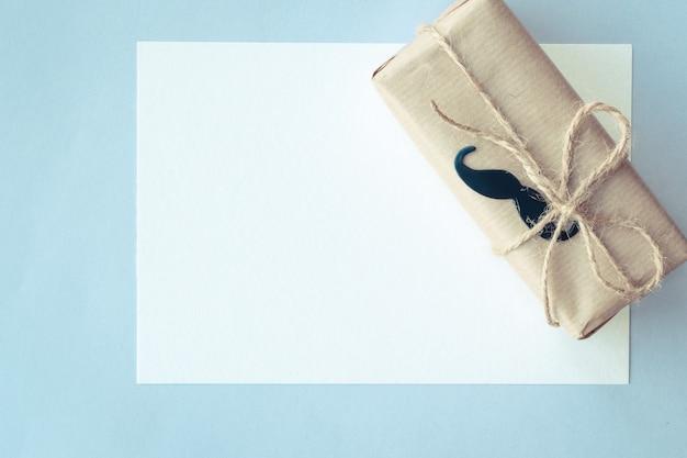 Dzień ojca. biała karta i pakiet prezentów owinięty papierem i liną