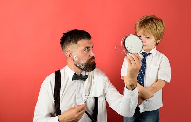 Dzień ojca mały chłopiec trzyma lustro dla ojca fryzjera do golenia brodaty mężczyzna w pielęgnacji brody dla fryzjera