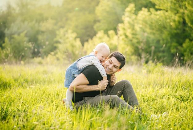 Dzień ojca. mężczyzna i jego córka spędzają wakacje w zielonym parku wieczorem o zachodzie słońca latem.