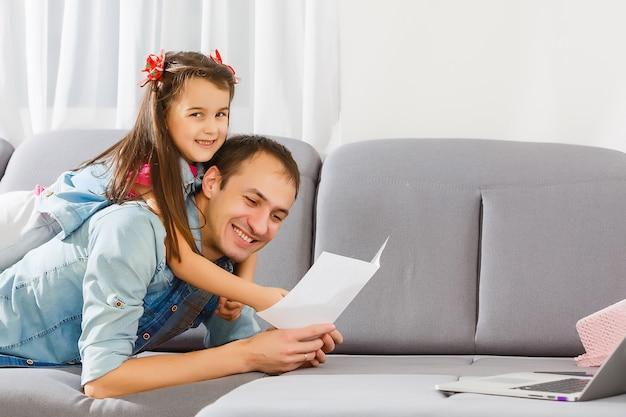 Dzień ojca. szczęśliwa rodzinna córka daje tata kartka z pozdrowieniami na wakacje