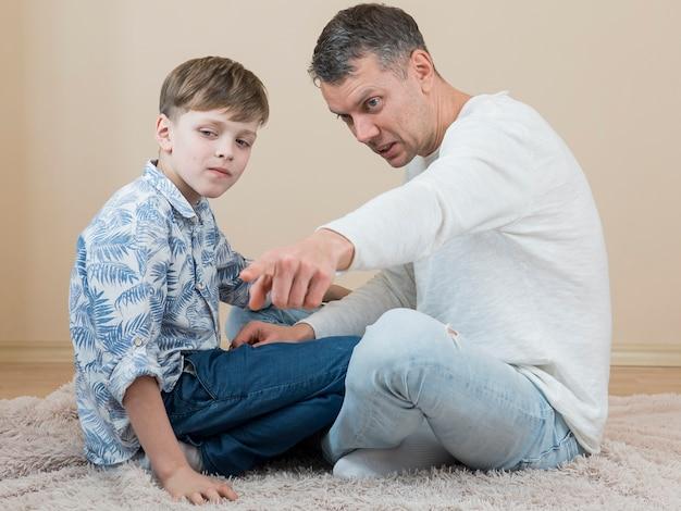 Dzień ojca tata i syn siedzą na podłodze