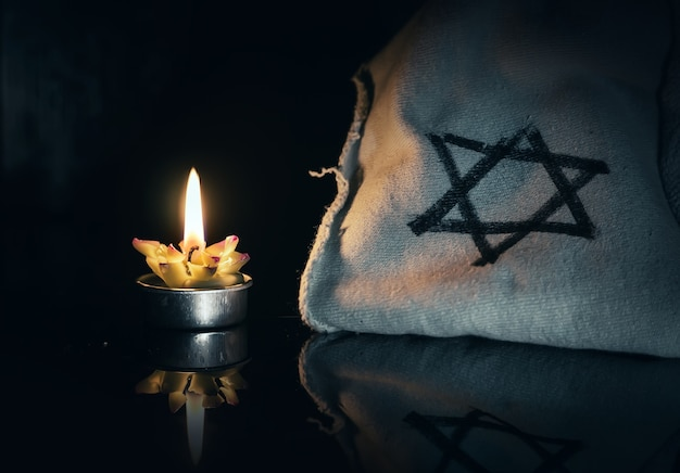 Dzień pamięci ofiar holokaustu płonących w nocy świecą i symbolem żydowskiej gwiazdy dawida