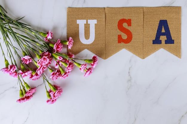 Dzień pamięci, świętowanie weteranów z tekstem usa na różowych kwiatach goździków