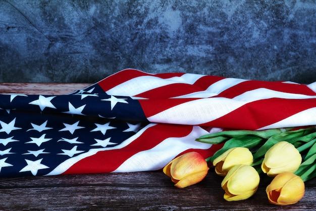 Dzień pamięci z amerykańską flagą i kwiat na drewnianym tle
