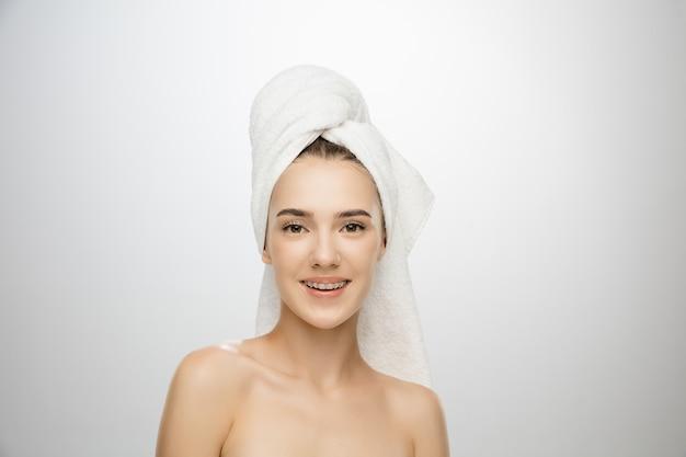 Dzień piękna kobieta nosi ręcznik na białym tle
