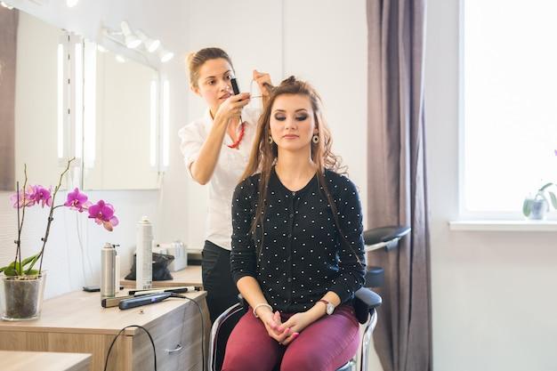 Dzień pracy w salonie kosmetycznym. fryzjer zajmuje się stylizacją włosów.