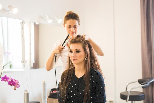 Dzień Pracy W Salonie Kosmetycznym. Fryzjer Zajmuje Się Stylizacją Włosów. Premium Zdjęcia