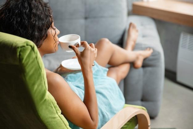 Dzień relaksu. afro-kobieta w ręcznik robi swoje codzienne zabiegi pielęgnacyjne w domu. siedząc na sofie, wygląda na zadowoloną, pije kawę i relaksuje się. pojęcie piękna, samoopieki, kosmetyki, młodości.