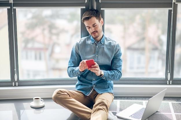 Dzień roboczy. ciemnowłosy mężczyzna pracuje w biurze i wygląda na zajętego