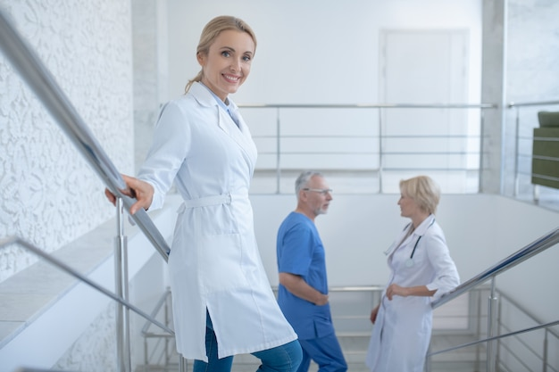 Dzień roboczy. grupa profesjonalnych lekarzy stojących na schodach szpitala, mówi