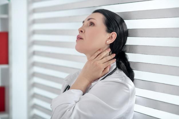 Dzień roboczy. kobieta ze stetoskopem trzymająca rękę przy szyi, stojąca plecami do okna z białą żaluzją, patrząc smutno.