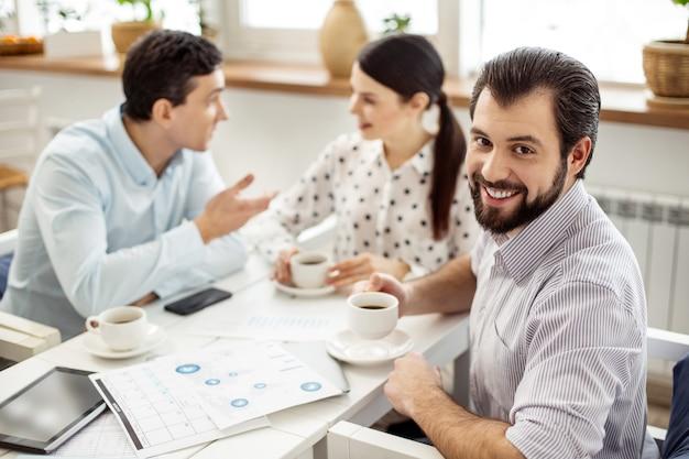 Dzień roboczy. przystojny, wesoły brodaty mężczyzna pije kawę i uśmiecha się, a jego koledzy rozmawiają w tle