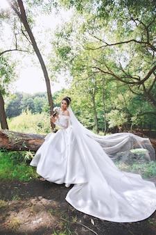Dzień ślubu. młoda piękna panna młoda z fryzurą i makijażem pozowanie w białej sukni i welon.