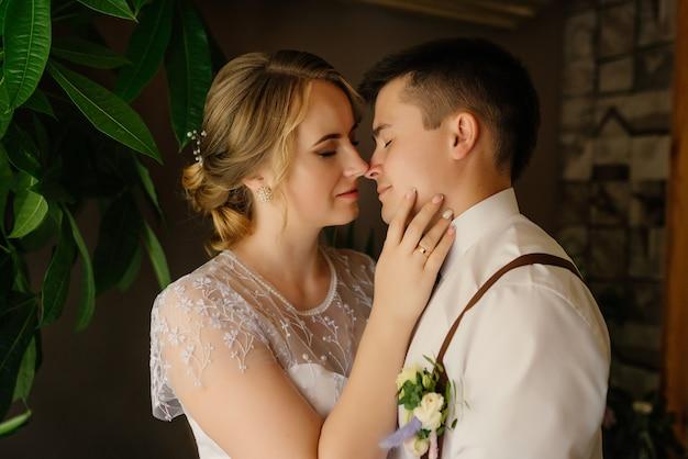 Dzień ślubu. nowożeńcy okazują sobie nawzajem uściski i dotykają nosa.